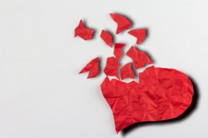 close up of paper broken heart on white background
